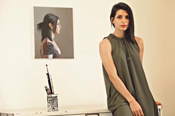 """סמאח שחאדה בסטודיו שלה בחיפה, על רקע דיוקן עצמי טרי. """"ראיתי בפייסבוק שאנשים מהכפר שלי שמו את הכתבות על הזכייה בפרס וכתבו 'אנחנו גאים בך'. הפתיעו אותי"""""""