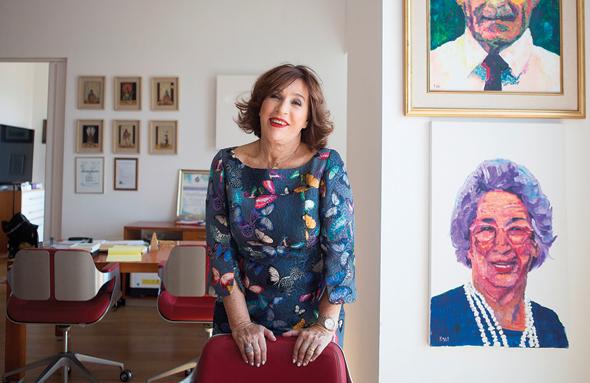 """ריכטר במשרדי מדינול, לצד תמונות של הוריה. """"כשהגרמנים נתנו חתיכת לחם, האסירות היהודיות סמכו רק על אמא שתחתוך בהגינות"""", צילום: תומי הרפז      איפור: לידור דהן מאק"""