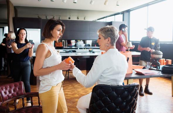 """יפית רפאל (משמאל בלבן), עם דליה מזור, בצילומי פרסומות לחברה. """"לכל אחד מהאחים תחום משלו"""""""