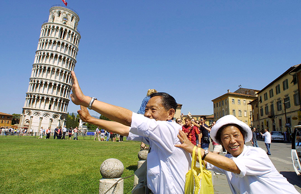 מוסף שבועי 28.6.18 דרקון עם דרכון תיירים סינים על רקע מגדל פיזה איטליה, צילומים: גטי אימג'ס