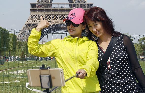 מוסף שבועי 28.6.18 דרקון עם דרכון תיירים סינים על רקע מגדל אייפל פאריז צרפת, צילומים: גטי אימג'ס