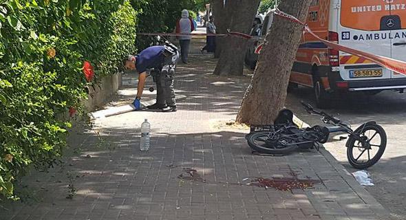 """שוטר מרים את הקרש שפגע ברוכב אופניים במקום הארוע, צילום: תיעוד מבצעי מד""""א"""