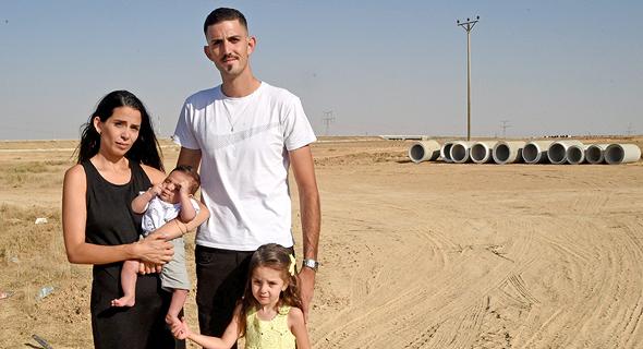 צחי ומור בן יאיר וילדיהם במגרש בשכונת הפארק בבאר שבע, 8 חודשים אחרי שזכו שם בדירה שתקים חברת אביסרור