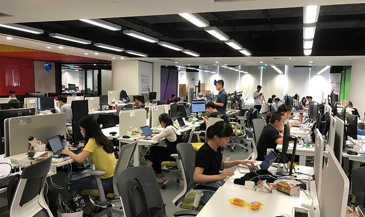 """עובדי Megvii ומסך ה""""עין"""" במשרדים בבייג'ינג. כולם מתגאים במה שהם עושים"""