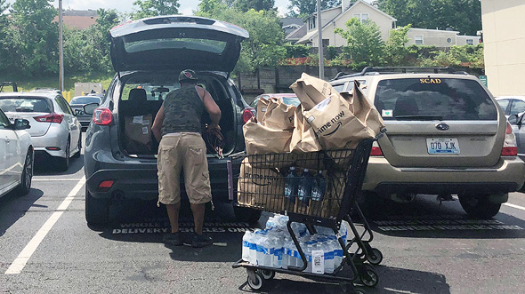 עובד של הול פודס מעמיס שקיות אמזון לרכב, צילום: רויטרס