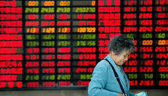 אישה סינית על רקע מסך בבורסה. הדעות חלוקות לגבי מי צריך לנהל את ענייני הכסף במשפחה