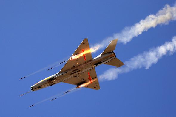 מטוס J7 סיני משגר רקטות לעבר מטרה קרקעית