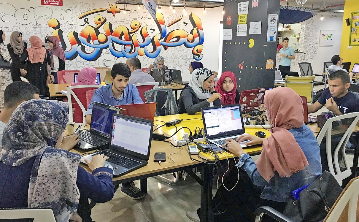 חלל עבודה של סטארט-אפ בעזה. ברקע הכיתוב בערבית: יזמים , צילום: (facebook (Gaza Sky Geeks