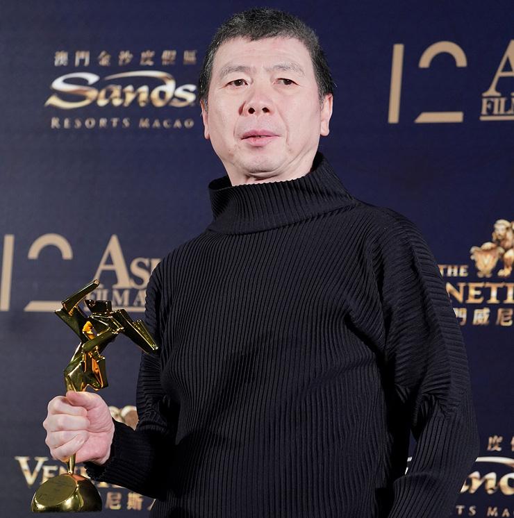 """הבמאי פנג במרץ, עם פרס הסרט הטוב ביותר בפסטיבל במקאו (על """"Youth""""). האשים את צ'ווי בקריסת מניות האולפנים"""