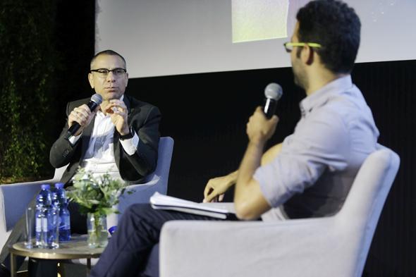 """מימין: כתב """"כלכליסט"""" עמרי מילמן ומנהל רשות המסים ערן יעקב בוועידה הכלכלית הלאומית"""