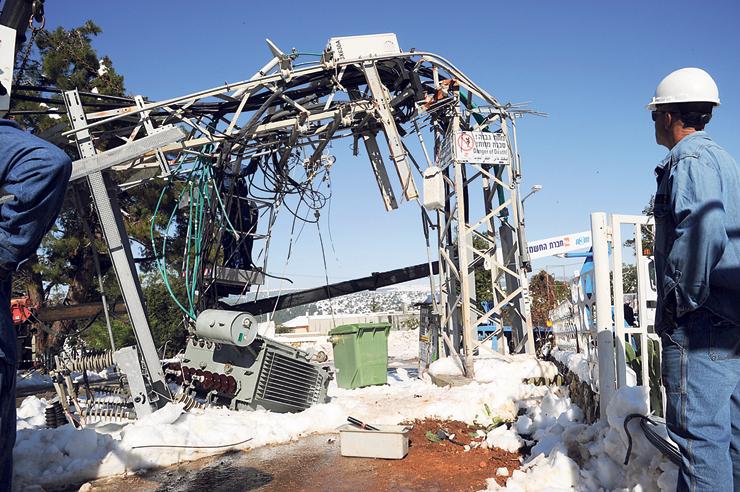 """עובדי החברה מתקנים נזקי סופה בכפר שמאי, דצמבר 2013. """"הטבת חשמל חינם היא ה"""
