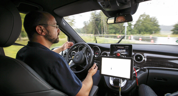 נהג עוזב את ההגה בניסוי רכב אוטונומי של מרצדס, צילום: בלומברג