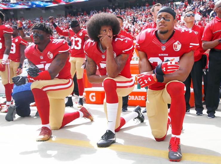 """קאפרניק (במרכז) כורע ברך בהשמעת ההמנון. """"בעלי הקבוצות מעדיפים שחקן שמסובך עם החוק על שחקן"""