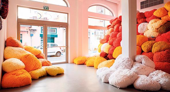 """מיצב """"Saffron Sentinel"""" בתערוכה. ערמות צבעוניות של סיבי פיגמנט אורגני"""