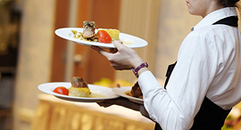 A waiter carrying food at a restaurant. Photo: Shutterstock