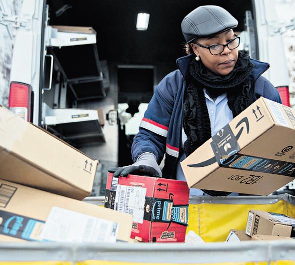 דוורית של שירות הדואר האמריקאי ממיינת חבילות של אמזון, צילום: בלומברג