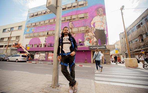 """גווטירז על רקע ציור הקיר שלו. """"ציירתי את פואד, השרת בבית הספר הסמוך שהכרתי השבוע. רוב האנשים סביבו בקושי מברכים אותו לשלום"""""""