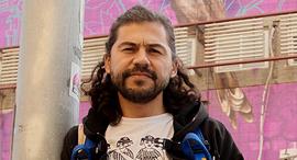 הצייר ליברה גווטירז על רקע ציור שלו ברחוב סלמה פנאי, צילום: תומריקו