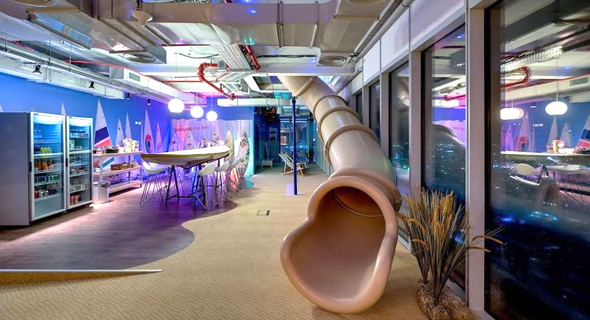 A slide leading to a furnished dining area at Google