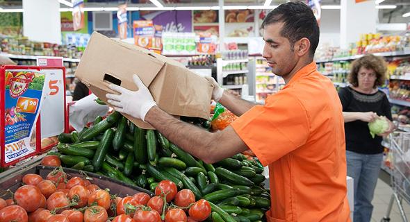 עובד ממלא את מגשי הירקות בסופרמרקט