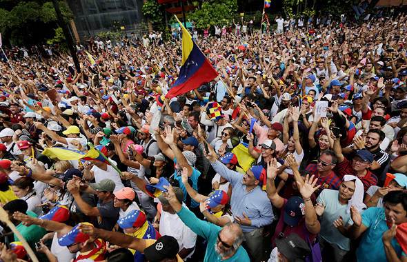 """מפגינים בקראקס נגד הממשל ב ונצואלה במהלך הכרזת יו""""ר האופוזיציה על עצמו כנשיא, צילום: איי פי"""