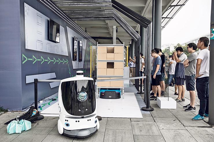 עובדים צופים ברובוטים לחלוקת חבילות במטה. השוק הבינלאומי מהווה רק 8% מכלל הכנסות החברה