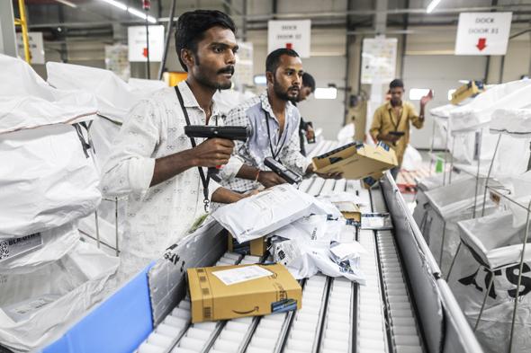 עובדי מרכז השילוח של אמזון בהיידראבד, הודו סורקים חבילות, צילום: בלומברג