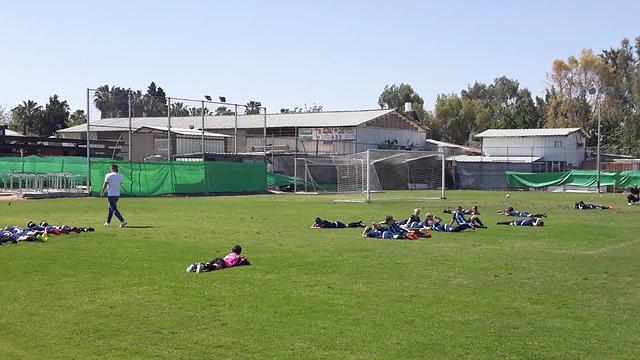 ילדים שוכבים על הדשא במשחק כדורגל, צילום: דימטרי סמיונוב