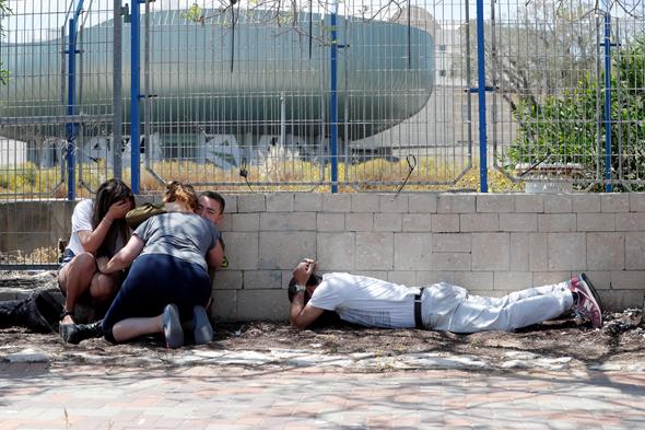 אזרחים מפוחדים מתגוננים מירי קאסמים, צילום: רויטרס