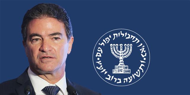 ראש מוסד יוסי כהן על רקע לוגו המוסד, צילום: אלכס קולומויסקי