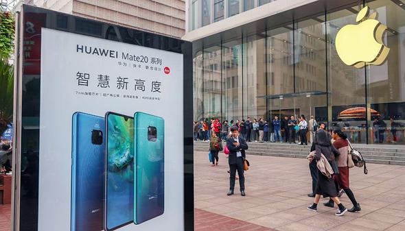 שלט של וואווי מול חנות של אפל בסין