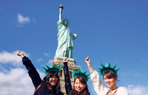 Chinese tourists pose in front of the Statue of Liberty. Photo: Reuters