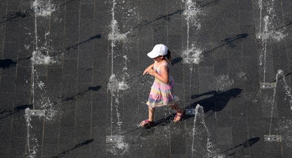 ילדה ב-Duisburg מנסה לצנן את עצמה במי המזרקות שבעיר, צילום: EPA