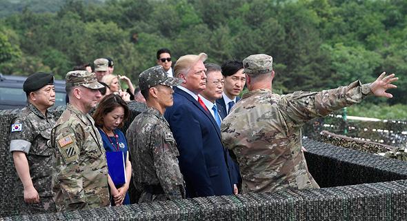 """נשיא ארה""""ב דונלד טראמפ עם שליט צפון קוריאה קים ג'ונג און וחיילים באזור המפורז, צילום: איי פי"""