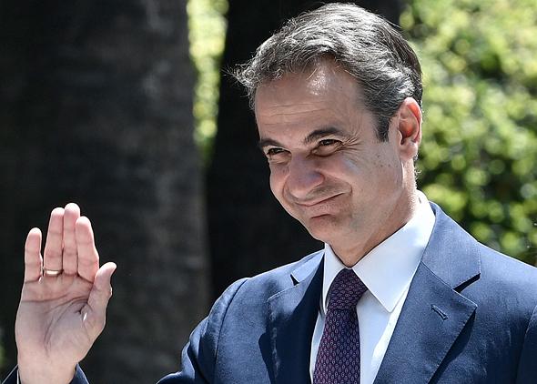 ראש ממשלת יוון קיריאקוס מנופף לשלום באצבעות סגורות. הקפידו לנהוג כמותו