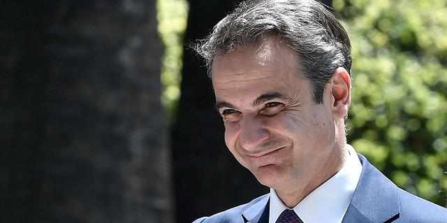 ראש ממשלת יוון קיריאקוס מנופף לשלום באצבעות סגורות. הקפידו לנהוג כמותו, צילום: איי אף פי