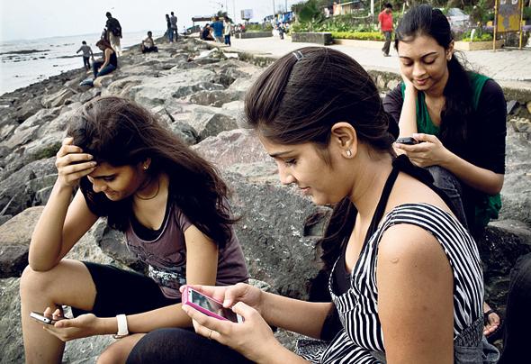 """צעירות בהודו משתמשמות בסמארטפון. """"זמן מסך זה דבר מגוון"""""""