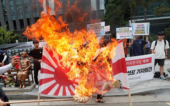 מפגינים בסיאול שורפים את דגל יפן האימפריאלית