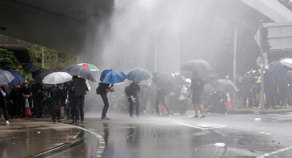 מטריות כמגן מפני זרנוקי מים, צילום: EPA