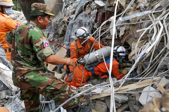 כוחות הצלה מנסים לאתר ניצולים בהריסות הבניין בן שבע הקומות שאכלס פועלים סינים עד שקרס, צילום: אי.אף.פי