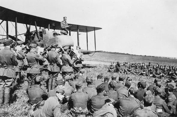 כומר צבאי נושא דרשה בפני אנשי טייסת בריטית מתא קדמי של מטוס FE2. המדחף נמצא מאחור, מתחת לכנף העליונה