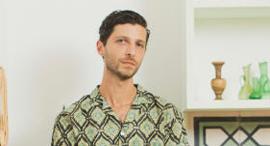 ג'ורדן נסאר על רקע פריטים מהתערוכה שלו, צילום: תומי הרפז
