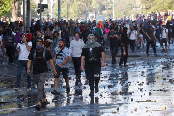 מפגינים בסנטיאגו בירת צ'ילה, השבוע. מדינה קטנה עם אי־שוויון גבוה ושירותים ציבוריים נשחקים