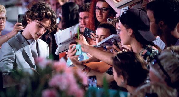 """טימותי שאלאמה חותם למעריצים בבכורת """"המלך"""" בוונציה. נהיה כוכב גם בזכות הרשתות החברתיות ובחירותיו בבנות זוג ובבגדים, צילום: Mondadori Portfolio"""