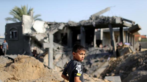 ילד וברקע מבנים שהותקפו ברצועת עזה