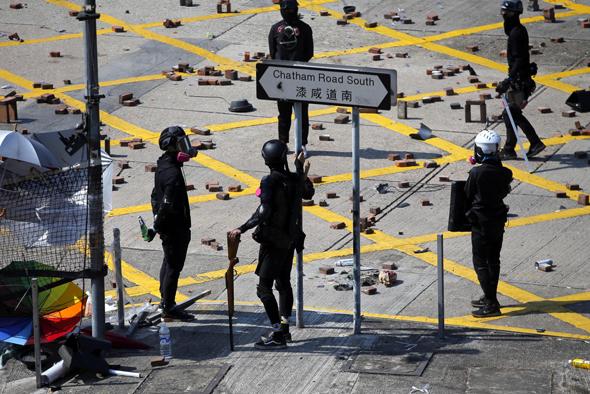 שוטרים מחוץ למכון הפוליטכני בהונג קונג, היום. סטודנטים הקימו מחסומים