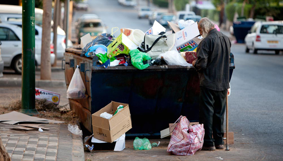 A man looking for food in a dumpster in Netanya, Israel. Photo: Tal Shachar