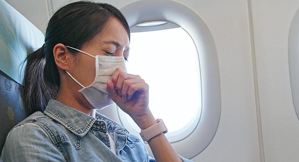 נוסעת משתעלת לתוך מסכה במהלך טיסה, צילום: שאטרסטוק
