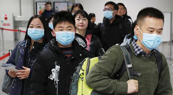 נוסעים מגיעים ליפן מסין עם מסיכות בעקבות התפרצות תסמונת הריאות הוויראלית, צילום: רויטרס