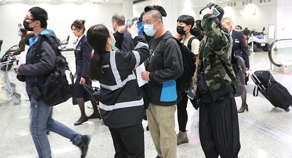 נוסיעם בשדה התעופה בהונג קונג עם מסיכות נגד הדבקות מווירוס הקורונה